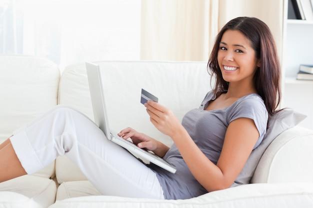 Mujer joven sonriendo a la cámara con tarjeta de crédito en las manos