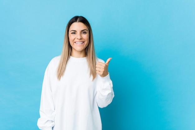 Mujer joven sonriendo y levantando el pulgar hacia arriba