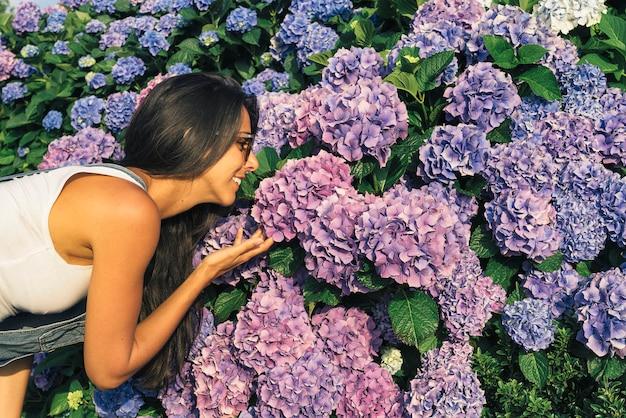 Mujer joven sonriendo mientras huele a flores