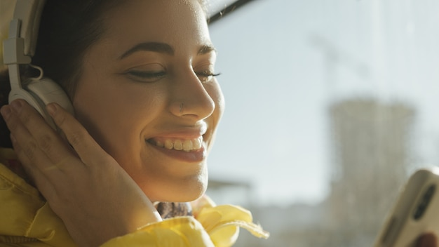 Mujer joven sonriendo mientras está de pie en el tren, tranvía o autobús. feliz pasajera escuchando música en un teléfono inteligente en el transporte público.