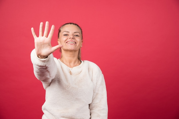 Mujer joven sonriendo y mostrando el número cinco con los dedos