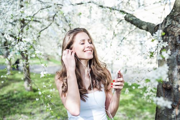 Mujer joven sonriendo y con los ojos cerrados escuchando música en el teléfono.