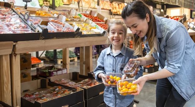 Mujer joven sonriente alegre con la pequeña hija que compra los tomates del globo en el mercado