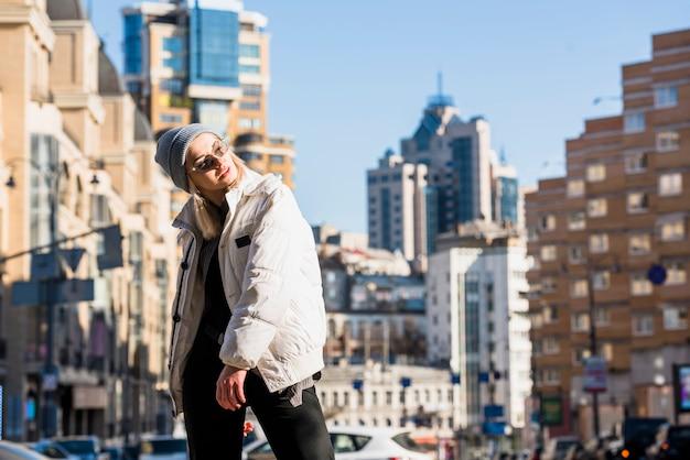 Una mujer joven sonriente atractiva que lleva los vidrios y la chaqueta que presentan delante de edificios