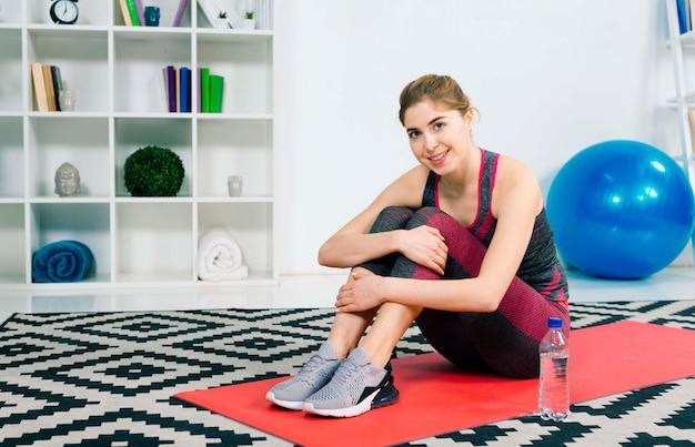 Una mujer joven sonriente atractiva que se sienta en la alfombra roja que mira a la cámara