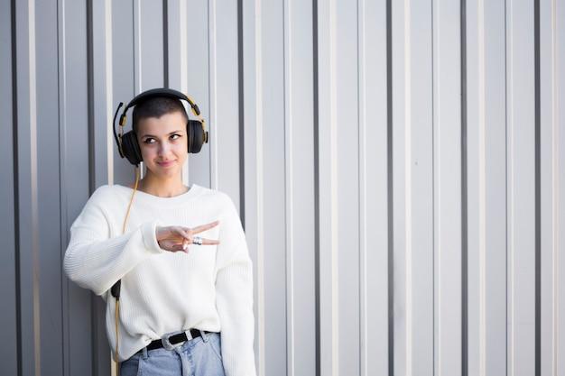Mujer joven sonriente con los auriculares y el peinado de la sacudida que gesticulan el signo de la paz