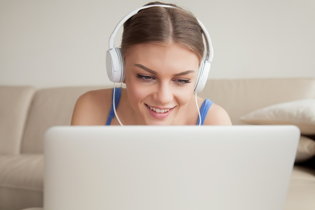 Mujer joven sonriente con auriculares usando laptop, headshot
