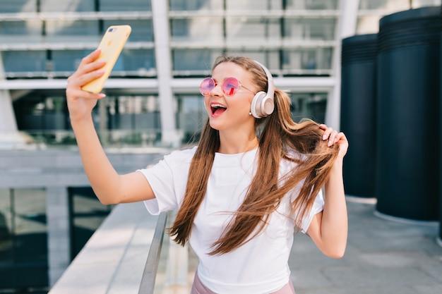Mujer joven sonriente y bailando haciendo un selfie con su teléfono inteligente y escuchando música en auriculares