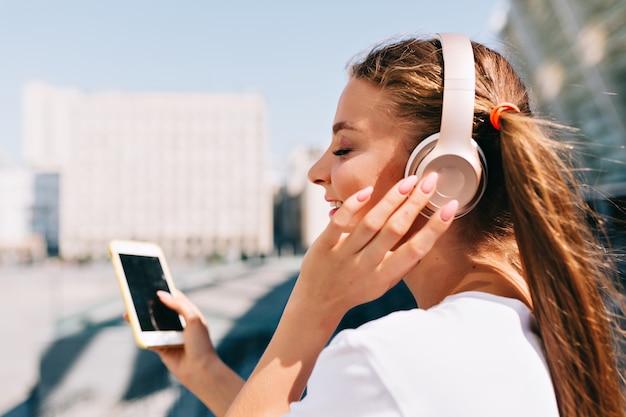 Mujer joven sonriente y bailando sosteniendo un teléfono inteligente y escuchando música en auriculares