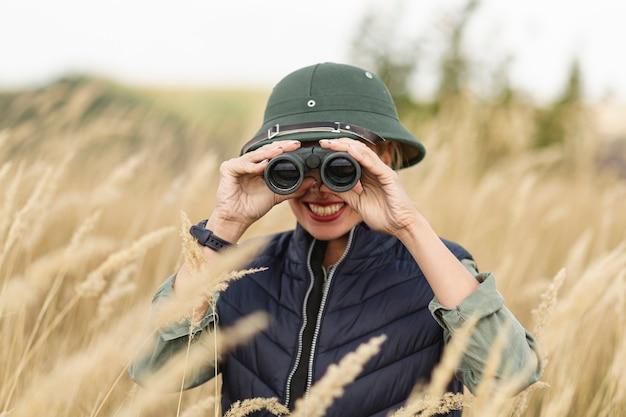 Mujer joven sonriente con binoculares