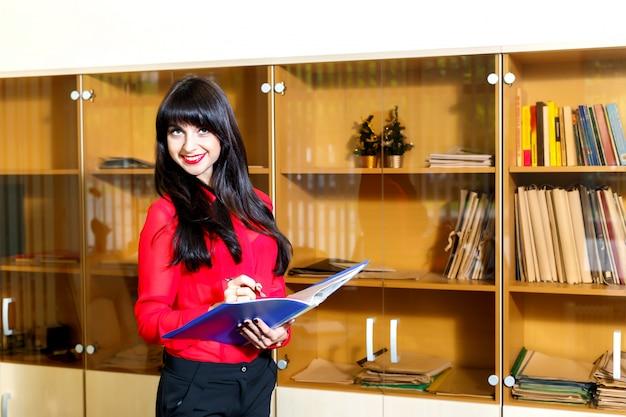 Mujer joven sonriente en una blusa roja con una carpeta de documentos en oficina