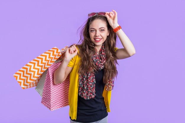 Mujer joven sonriente con los bolsos de compras contra el contexto púrpura