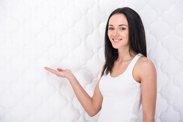 Mujer joven sonriente con colchón ortopédico.