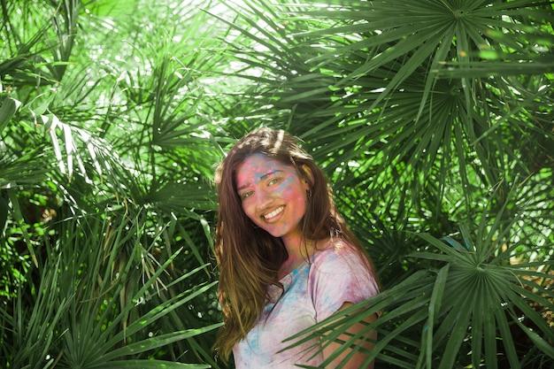 Mujer joven sonriente con color holi en su cuerpo de pie entre las hojas de palma verde