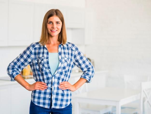 Mujer joven sonriente confiada que se coloca en cocina