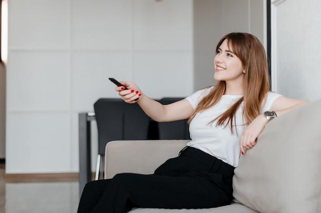 Mujer joven sonriente con control remoto desde la televisión sentado en un sofá en casa en el apartamento