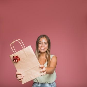 Mujer joven sonriente dando bolsa de compras con lazo rojo