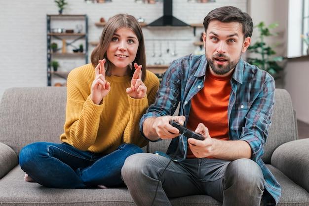 Mujer joven sonriente con los dedos cruzados que se sientan cerca del hombre que juega al videojuego