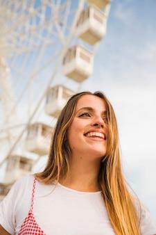 Mujer joven sonriente delante de la rueda de ferris