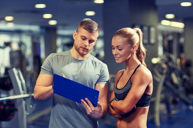 Mujer joven sonriente con entrenador personal en gimnasio