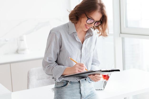 Mujer joven sonriente escribiendo en un portapapeles