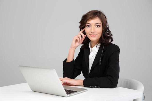 Mujer joven sonriente feliz bastante rizada en chaqueta negra con el auricular que se sienta y que trabaja usando la computadora portátil