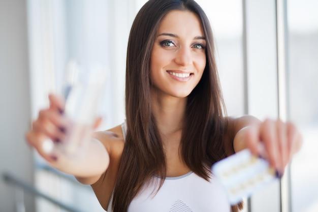 Mujer joven sonriente feliz que toma suplemento dietético