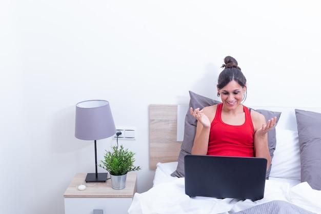 Mujer joven sonriente feliz, relajándose en su cama con la computadora portátil. abriendo los brazos sorprendidos