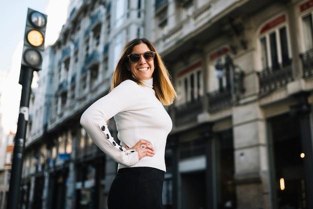 La mujer joven sonriente con las gafas de sol acerca a edificios en ciudad