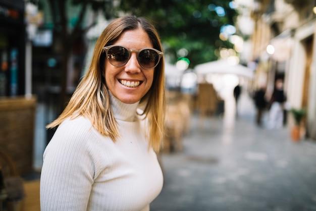 Mujer joven sonriente con las gafas de sol en la calle en ciudad