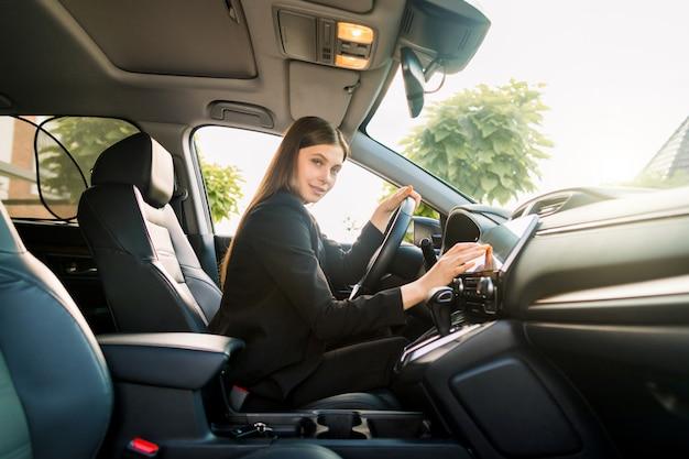 Mujer joven sonriente hermosa en el traje de negocios negro que conduce el coche, muchacha atractiva que se sienta en automóvil, retrato al aire libre del verano.