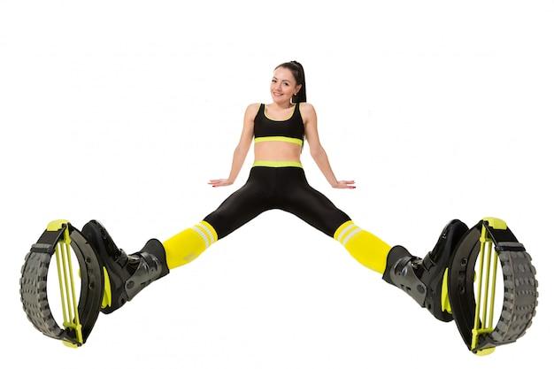 La mujer joven sonriente en kangoo salta los zapatos que sientan las piernas separadas.