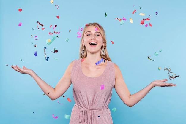 Mujer joven sonriente lanzando confeti