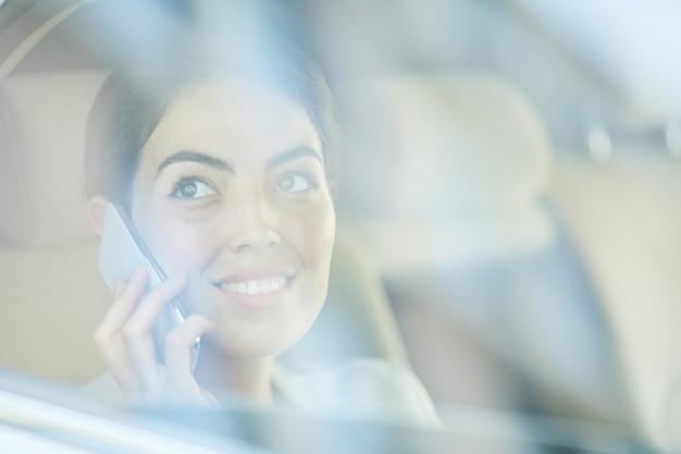 Mujer joven sonriente llamando desde taxi