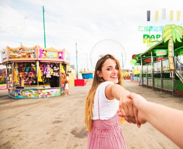 La mujer joven sonriente lleva a cabo la mano de su amigo que camina en el parque de atracciones