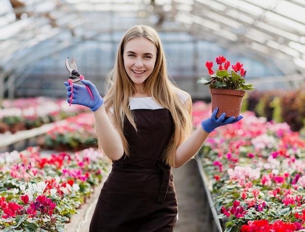 Mujer joven sonriente llevando flores