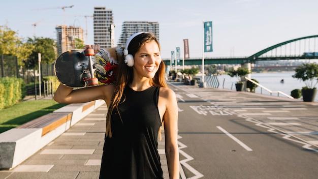 Mujer joven sonriente con el monopatín que escucha la música en el auricular