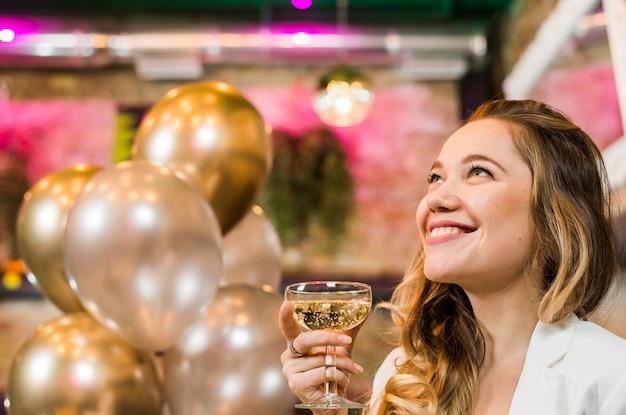 Mujer joven sonriente pensativa que sostiene el vidrio del whisky en barra