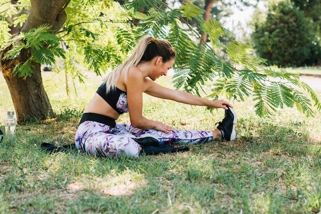 Mujer joven sonriente practicando yoga en el parque