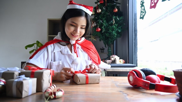 Mujer joven sonriente preparándose para la navidad y envolver regalos en casa.