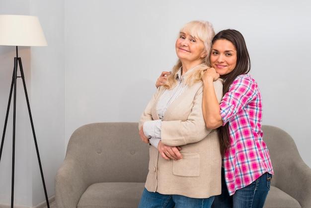 Mujer joven sonriente que abraza a su madre mayor de detrás que se coloca delante del sofá