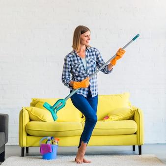 Mujer joven sonriente que actúa como tocar la guitarra en la sala de estar