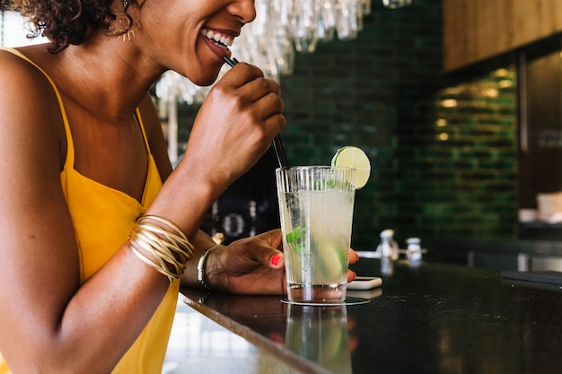 Mujer joven sonriente que bebe mojito en la barra del bar en el restaurante