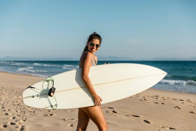 Mujer joven sonriente que camina con la tabla hawaiana en la costa