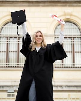 Mujer joven sonriente que celebra su graduación