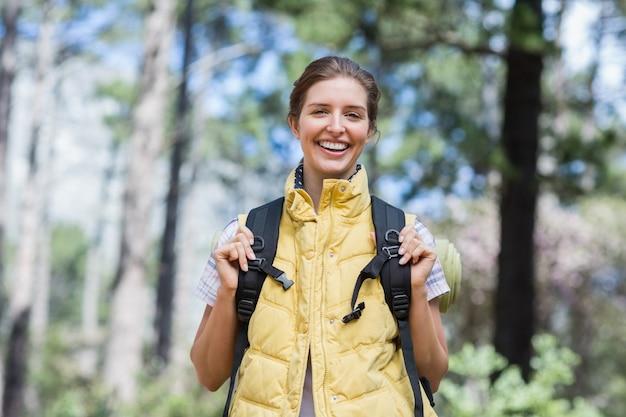 Mujer joven sonriente que se coloca en bosque