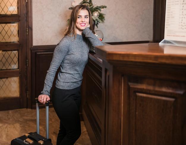 Mujer joven sonriente que se coloca cerca del mostrador de recepción en hotel