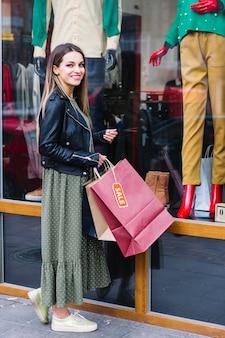 Mujer joven sonriente que se coloca delante de la exhibición de la ventana que sostiene bolsos de compras