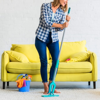 Mujer joven sonriente que se coloca delante del sofá que sostiene la fregona