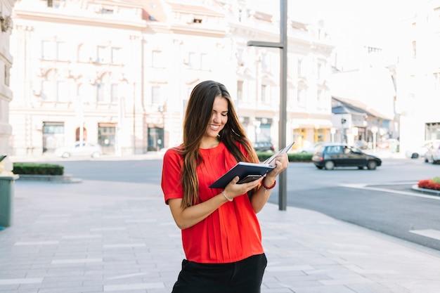 Mujer joven sonriente que se coloca en el diario de la lectura de la acera